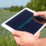Zwei Männerhände halten ein Tablet. Darauf steht der Schriftzug Smart Country. Im hintergrund Blick auf Wiesen und Wälder.