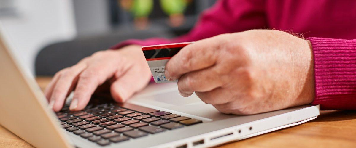 Zwei Männerhande auf der Tastatur eines Laptops. Der Man hat einen roten Pullover an. Eine der beiden Hände hält eine Bankkarte.