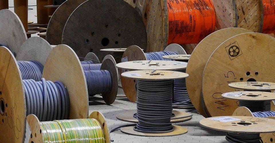 Zahlreiche große Kabeltrommeln mit Kabeln in unterschiedlichen Farben