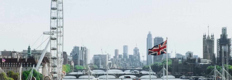 Blick auf die Themse in London und viele Brücken. Im Vordergrund weht eine britische Flagge.