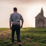 Auf einem Hügel auf einer Wiese steht eine einsame kleine Kirche. Dahinter geht die sonne unter. Ein Mann mit kariertem Hemd läuft auf die Kirche zu.