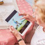 Foto aus der Vogelperspektive: eine ältere Frau hält ein Tablet. Auf dem Tablet ist eine Familie mit kleinen Kindern zu sehen.