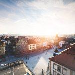 Marktplatz einer deutschen Kleinstadt. Hinter dem Kirchturm ist die Silhouette der Sonne.