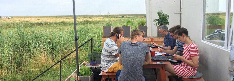 Fünf Personen sitzen auf der Terrasse des CoWorkLand-Containers. Alle arbeiten an ihren Geräten. Im Hintergrund sieht man nichts als Felder.