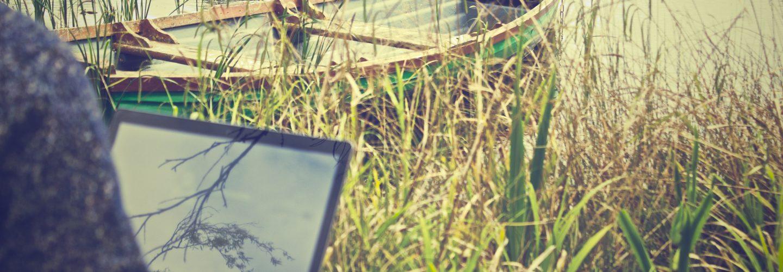 Ein Mann sitzt mit seinem Laptop am See. Hinter dem Bildschirm des Laptops ist ein kleines Holzboot im See.