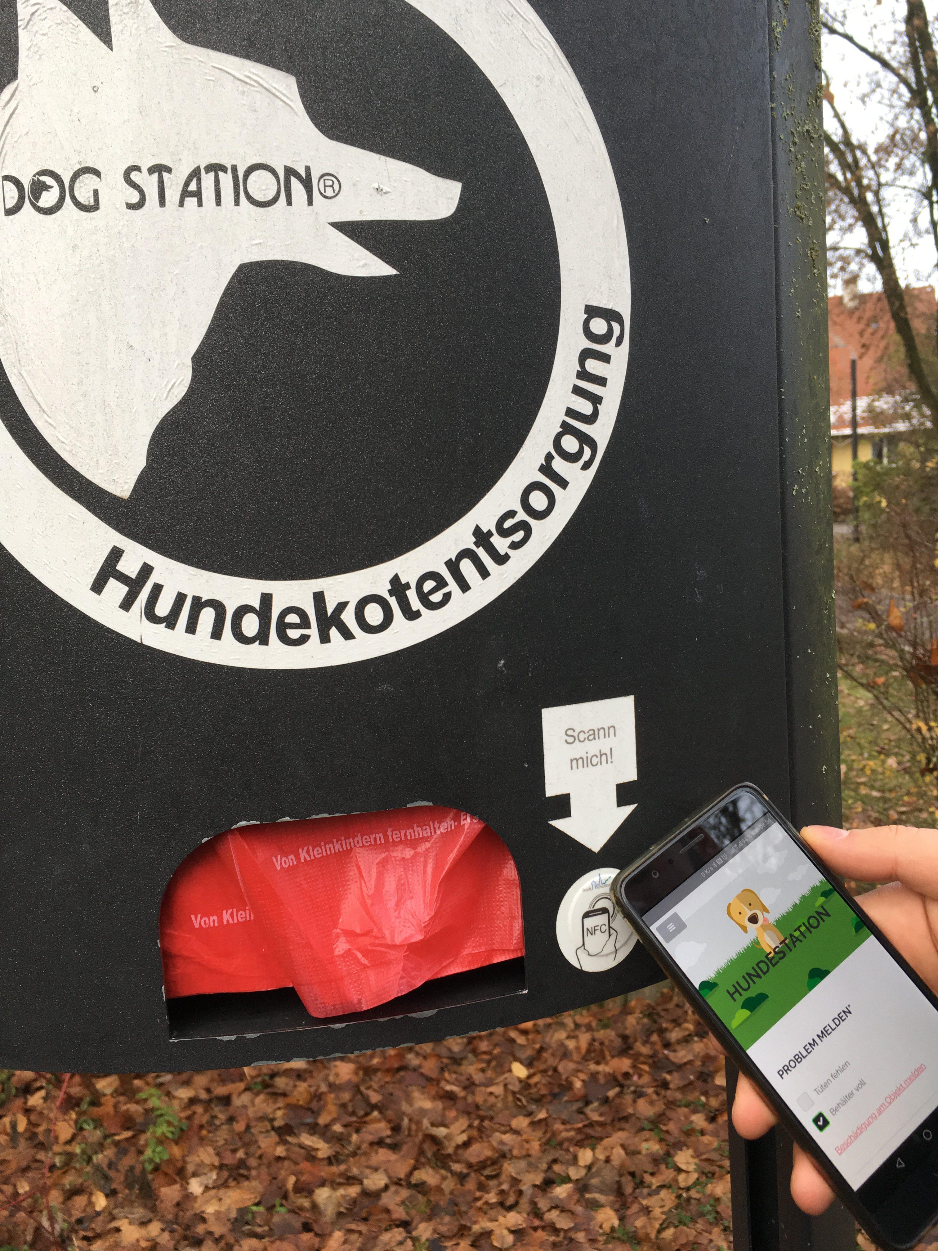 Eine Vorrichtung mit Tüten für Hundekot. Daran hängt ein NFC-Chip. Ein Smartphone wird an den Chip gehalten. Auf dem Smartphone erscheint die App von Eine Stadt.