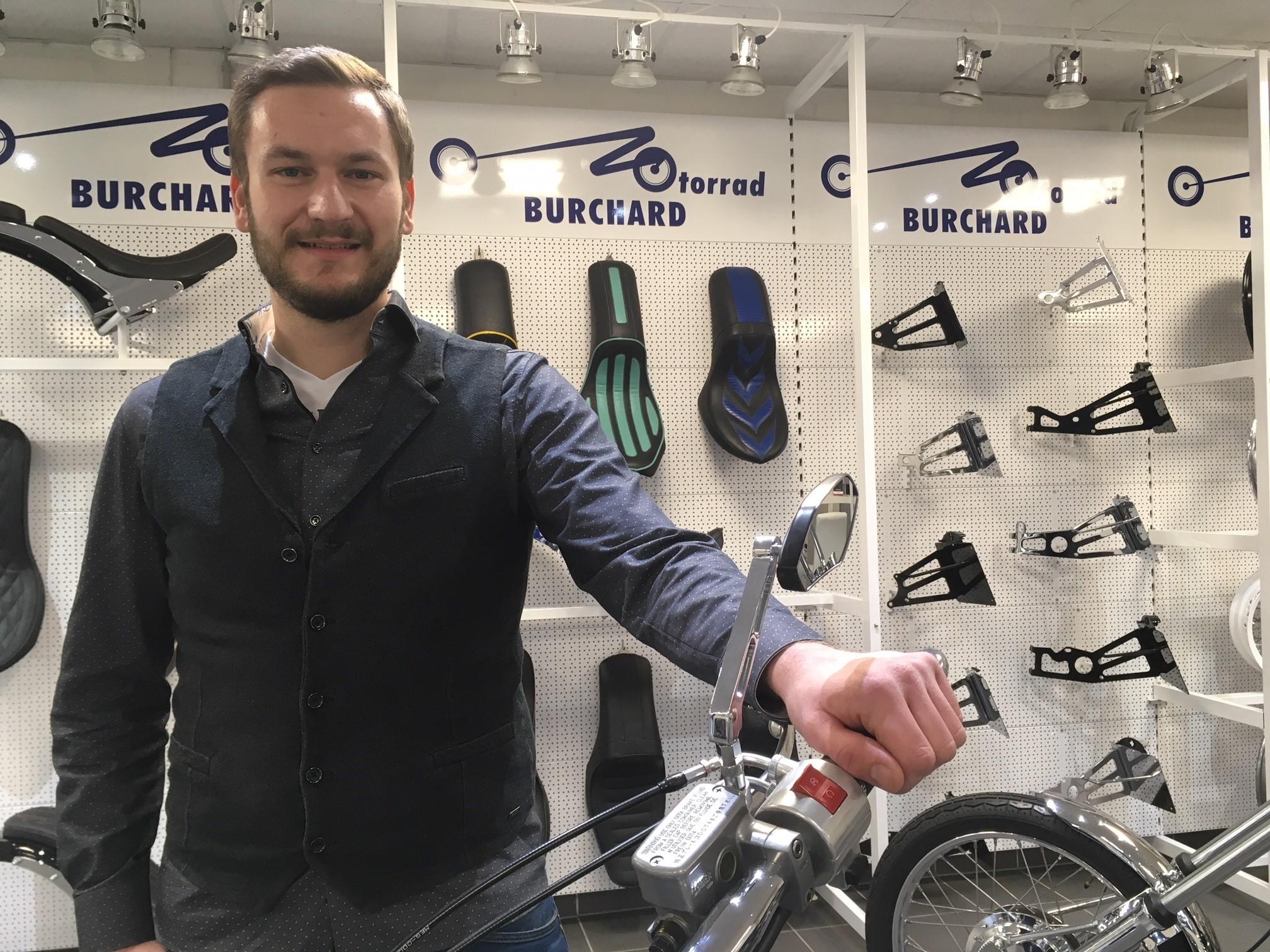 Sebastian Burchard, Geschäftsführer der Motorrad Burchard GmbH in seinem Geschäft, hinter einem Motorrad stehend.