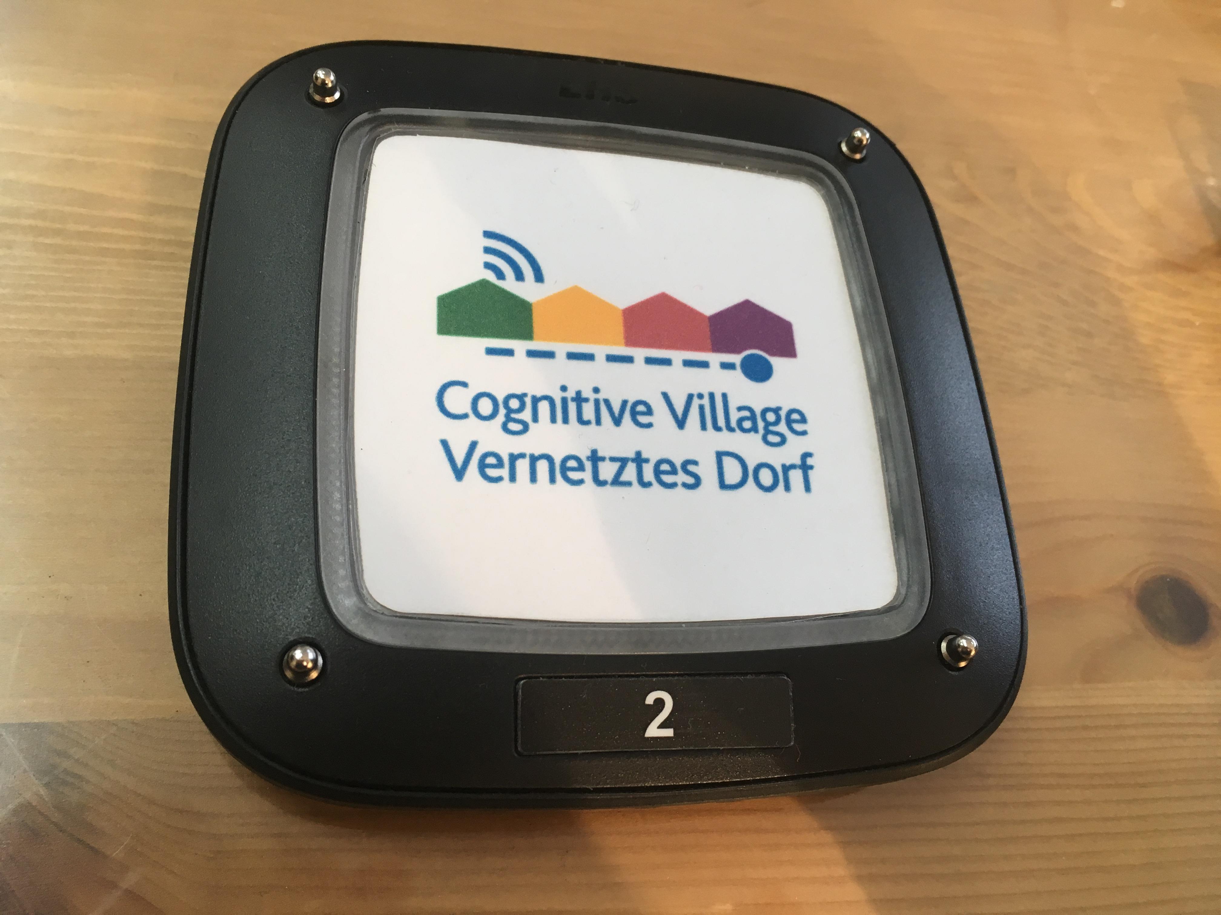 """Ein Pager liegt auf einem Tisch. Darauf abgebildet das Logo und Schriftzug von """"Cognitive Village - Vernetztes Dorf""""."""