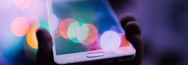 Eine Hand hält ein Smartphone hoch. Auf dem Display und im Hintergrund spiegeln sich schillernde Farben, ähnlich wie in einem Kaleidoskop