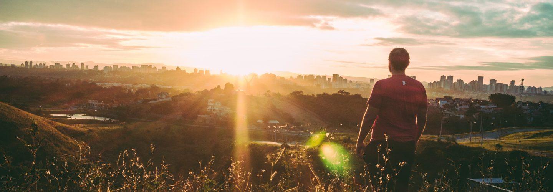 Ein Mann steht auf einem Berg. Die Kameria filmt ihn von hinten. Er schaut aus der Ferne auf eine Stadt. Die Sonne geht gerade unter und die Sonne strahlt noch einmal kräftig.