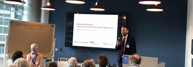 Julian Stubbe präsentiert den Teilnehmenden erste Ergebnisse aus der Studie. Herr Stubbe steht neben einem Monitor. Vorne links sitzt Dagmar Hirche.