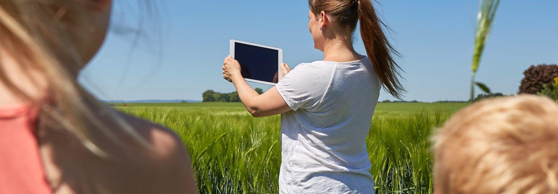 Eine Frau steht vor einem Maisfeld. Sie hält ein Tablet hoch. Vorne im Bild sind zwei Kinder. Man sieht nur ihren Rücken und Hinterköpfe.