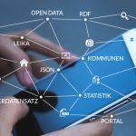 Eine Person bedient ein Smartphone. Man sieht die beiden Hände und das Smartphone. Über das Display drüber gelegt sind verschiedene Schlagwörter, wie z.B. Kommunen, Lizenz, Open Data, die verbunden sind.