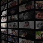 Eine Frau mit längeren Haaren schaut auf eine Wand, auf der sehr viele kleinere Monitore mit zahlreichen Gesichtern abgebildet sind. Das Bild ist in schwarz-weiß gehalten.
