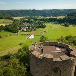 Drohnen-Luftbildaufnahme der Burg Blankenberg in Hennef. Oben auf der Burg ist eine Person,, die an einer der zahlreichen Funkantennen steht.