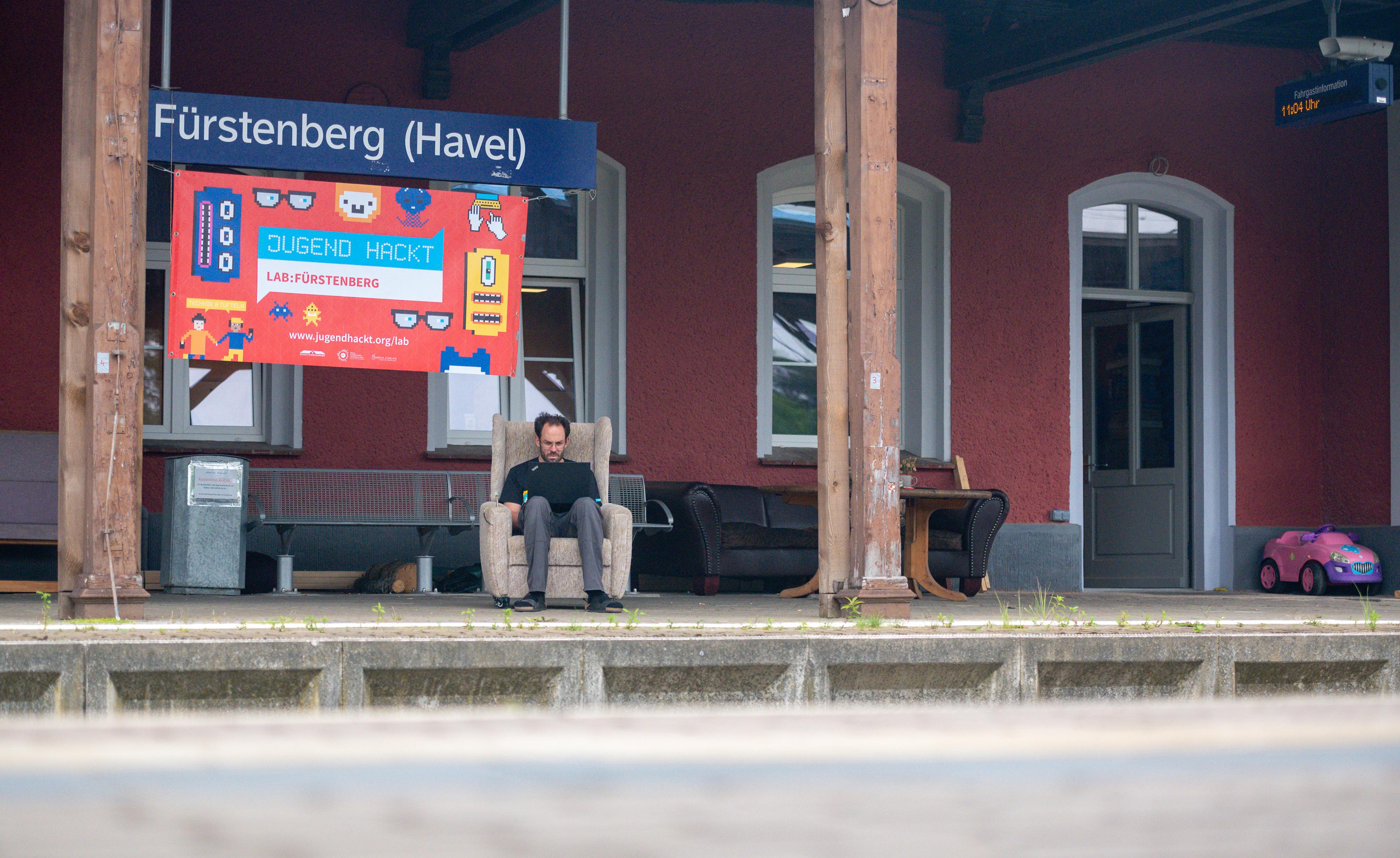 """Daniel-Domscheit-Berg sitzt mit einem Laptop auf den Knien auf einem alten Sessel am Gleis des Bahnhofs, dem heutigen Verstehbahnhof. Unter dem Bahnhofsschild mit der aufschrift """"Fürstenberg/Havel"""" ist noch ein großes Schild mit der Aufschrift """"Jugend hackt""""."""