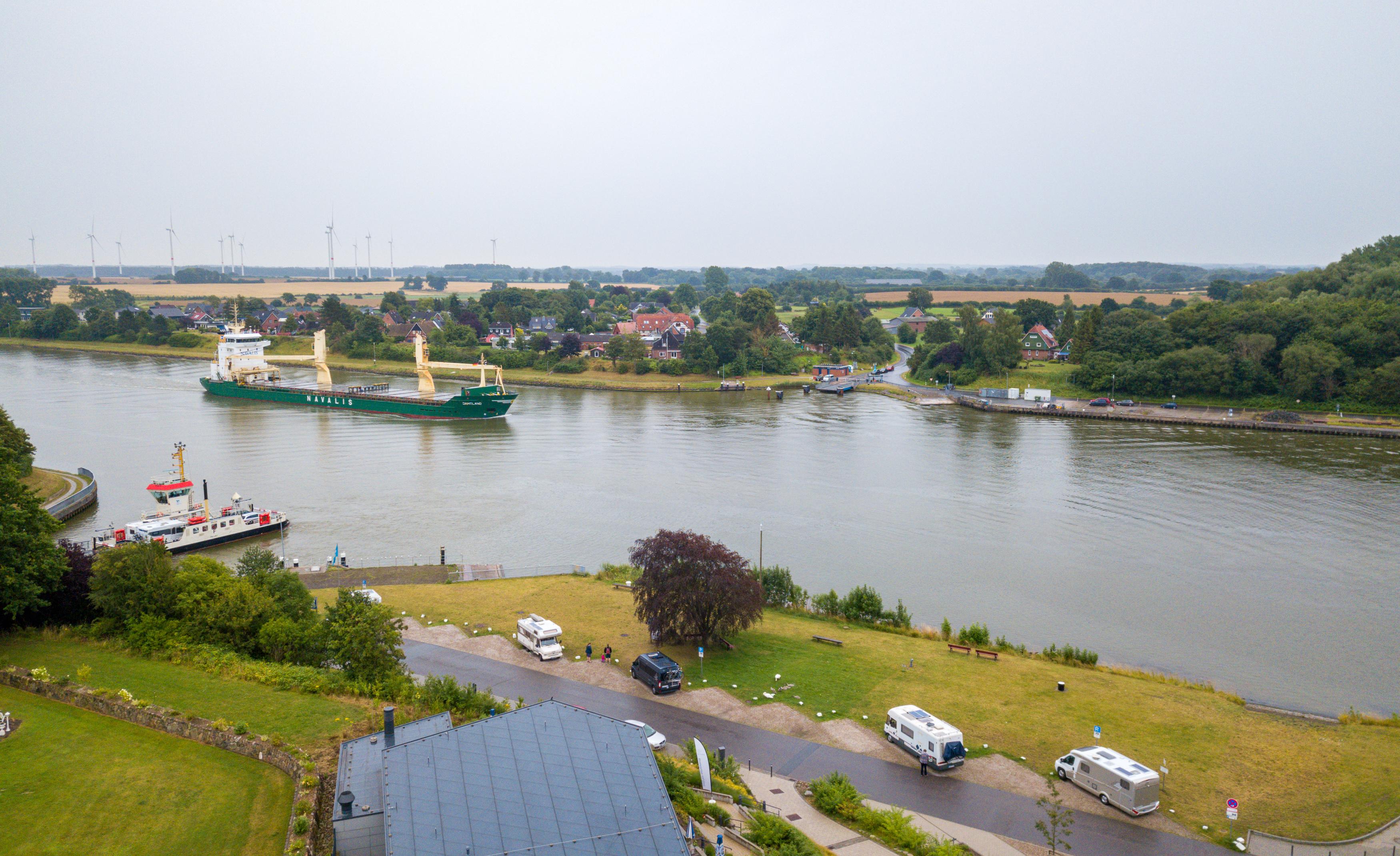 Luftaufnahme aus dem Amt Hüttener Berge. Im Vordergrund ist ein größeres Gebäude mit ein paar PKWs davor. Im oberen Teil des Bildes ein Fluss mit einem Frachtschiff.