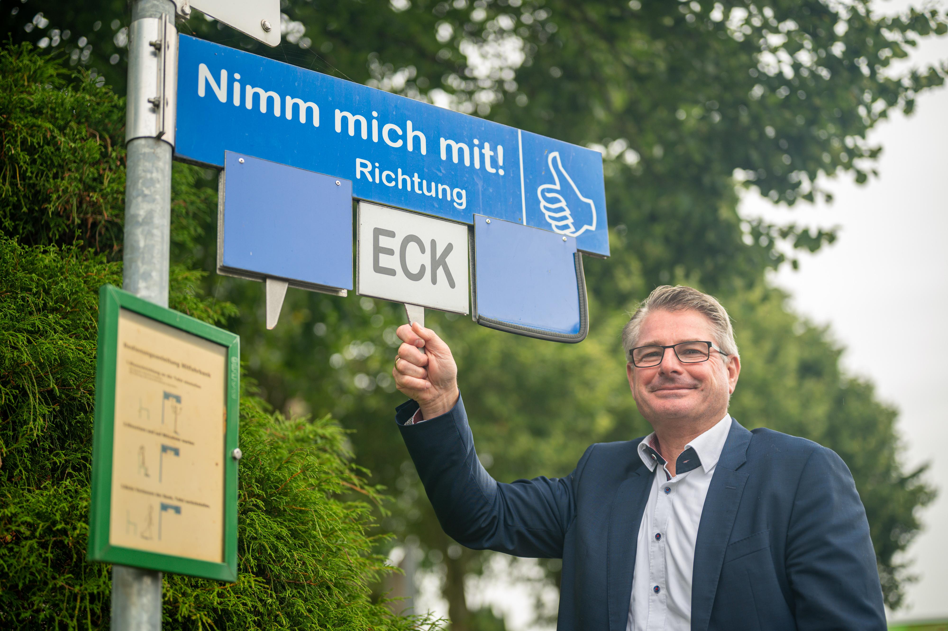 """Amtsdirektor Andreas Betz an der Mitfahrbank. Er hält die rechte Hand an ein Schild mit der Abkürzung ECK für Eckernförde. Darüber ist ein blaues Schild mit der Aufschrift """"Nimm mich mit!""""."""