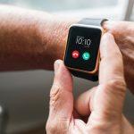 Am linken Arm eines älteren Menschen ist eine Smartwatch. Man sieht, dass ein Anruf auf WhatsApp eingeht. Die rechte Hand der Person fastt mit Daumen und Zeigefinger an die Uhr.