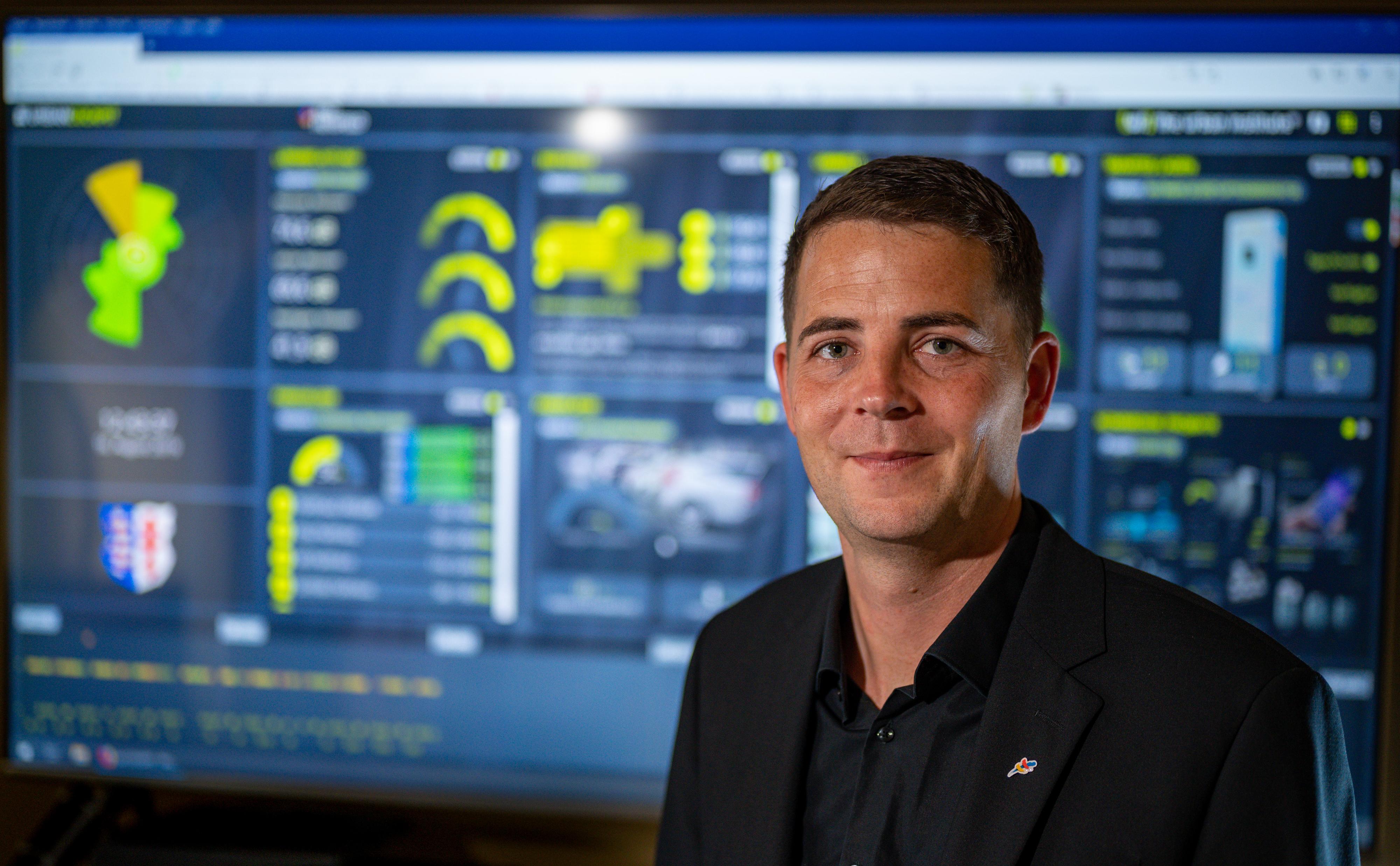 Martin Steimar steht vor einem großen Monitor, auf dem zahlreiche Daten im Urban Cockpit zusammenlaufen und visualisiert werden.