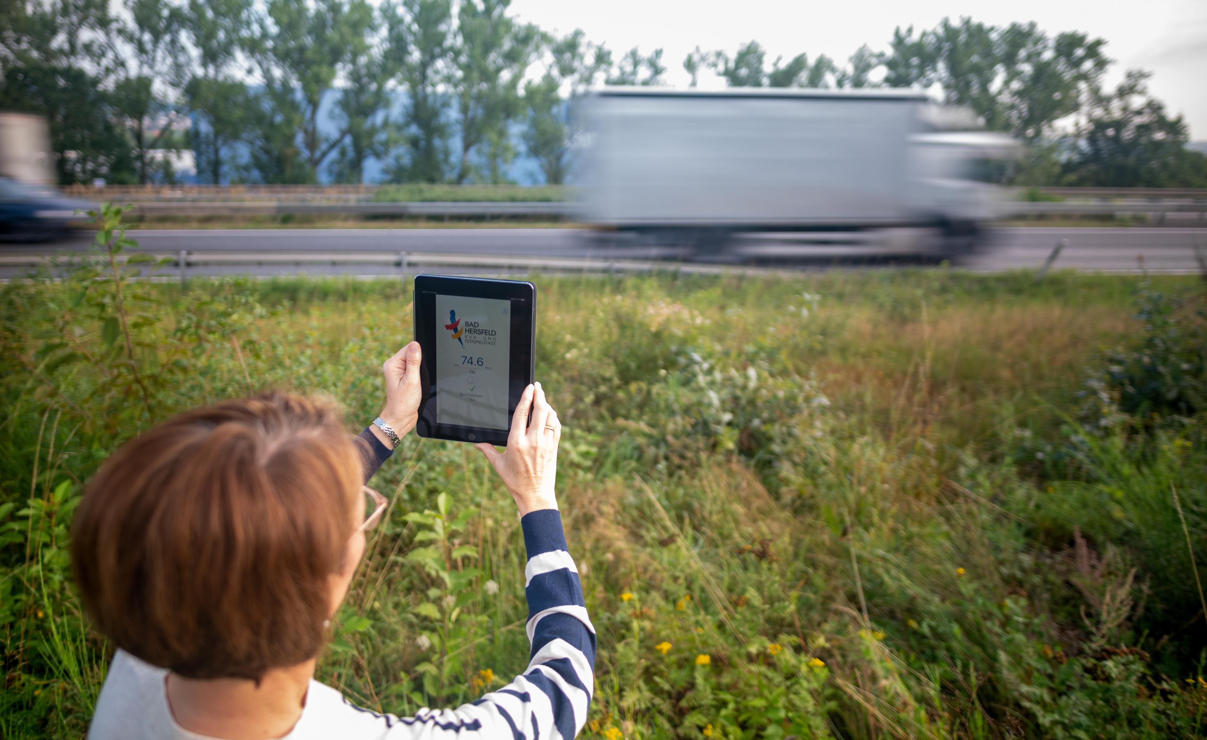 Die Bad Hersfelderin Katja Sippel hält ihr Tablet in die Luft und misst mit einer App den Verkehrslärm an der A4. Frau Sippel ist in der unteren Hälfte des Bildes, in der oberen Hälfte sind die verschwommenen Konturen eines vorbeifahrenden LKWs.