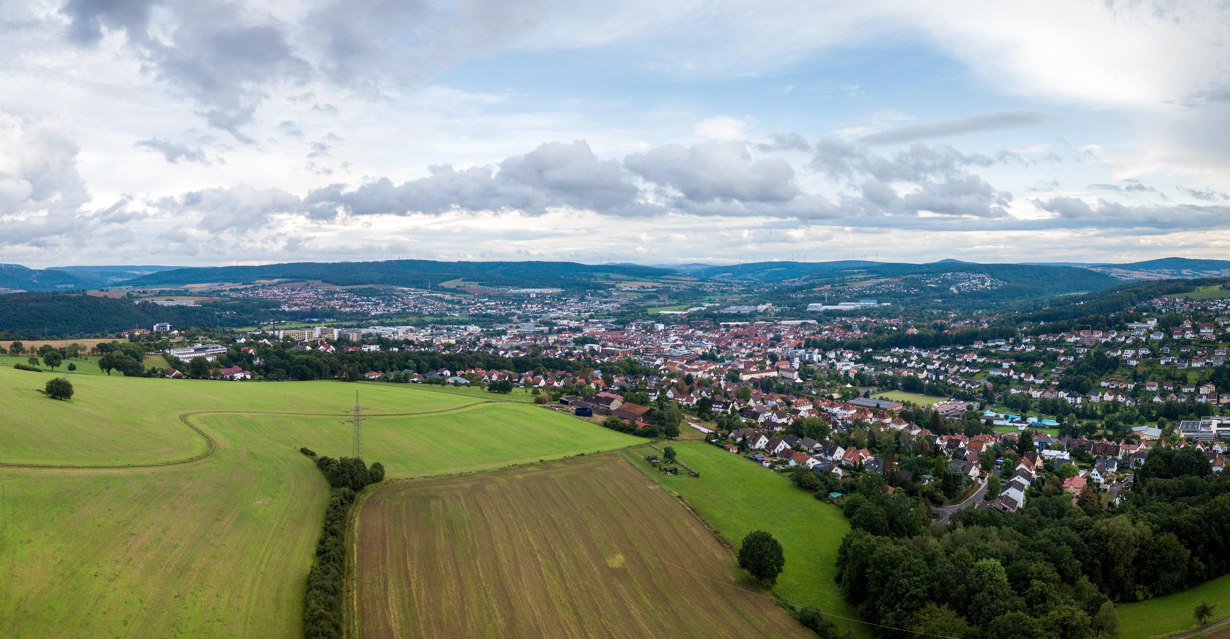 Lauftaufnahme aus einer Drohne. Im Vordergrund sind grüne Wiesen. Weiter am Horizont ist die hessische Mittelstadt Bad Hersfeld.
