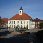 Der Markplatz in Angermünde. Im Zentrum des Fotos steht ein altes, weißes Gebäude, das aber hübsch renoviert wurde.