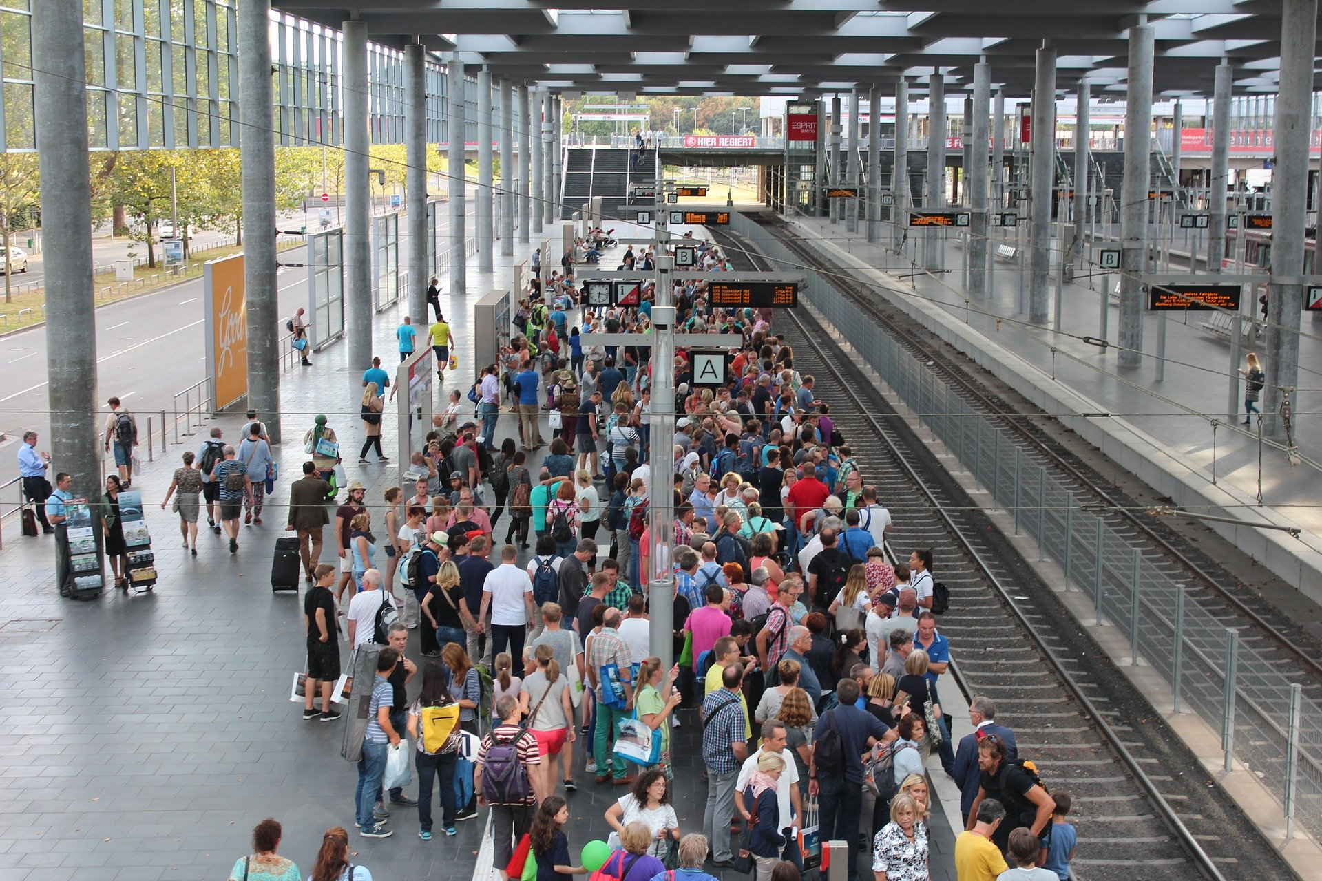 Auf einem Bahnsteig warten zahlreiche Menschen auf den nächsten Zug.