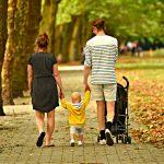 Eine Kleinfamilie spaziert mit einem Kleinkind in einem Park.
