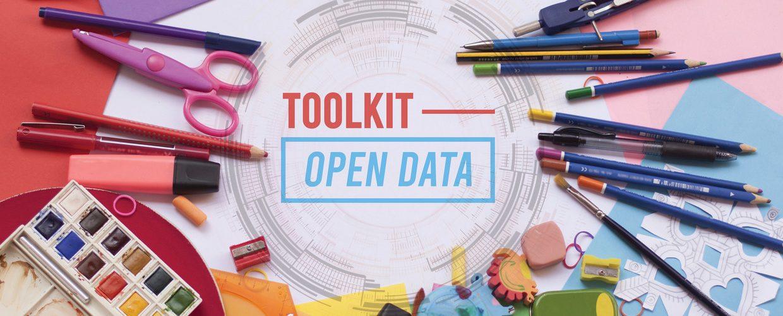 """Ein Schreibtisch mit vielen Schreibutensilien wie etwas bunte Stifte. In der Mitte ist eine Grafik mit dem Schriftzug """"Toolkit - Open Data"""""""