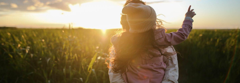 Sonnenuntergang im Hintergrund und ein landwirtschaftlich genutztes Feld im Vordergrund. Ganz vorne ist eine Mustter mit einem Kind auf dem Arm. Man sieht nur den Rücken des Kindes.