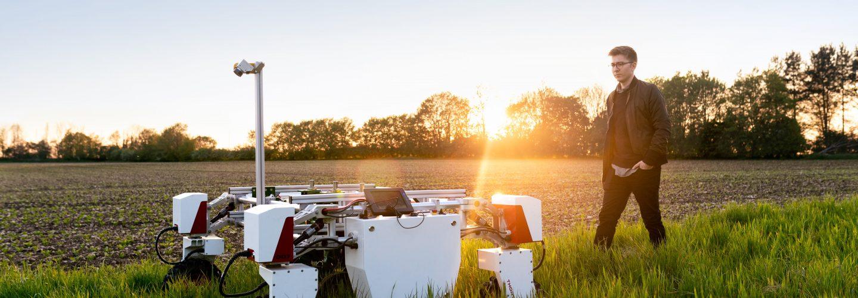 Männlicher Ingenieur mit einem Landwirtschaftsroboter auf einem Feld. Im hintergrund geht die Sonne unter.
