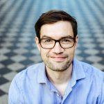 Portraitfoto von Frederik Fischer mit hellblauem Hemd.