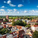Blick aus der Luft auf eine kleine oder mittelgroße Stadt. Es sind viele rote Backsteinhäuser zu sehen. Am Horitont ist viel grün zu sehen.