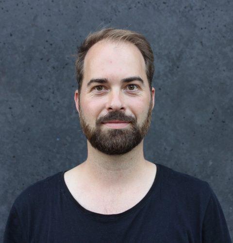 Portraitfoto von Philipp Hentschel vor einem grauen Hintergrund.