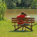 Ein Paar sitzt auf einer Bank und schaut auf einen See.