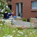 Auf einer Terrasse mit einigen Sitzmöglichkeiten sitzen drei junge Leute, zwei davon mit Laptop.