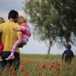Ein Vater trägt links und rechts seine beiden kleinen Mädchen durch ein Feld. Weiter vorne sind zwei Bäume zu sehen. Auf die läuft sein vorauseilender Sohn zu.